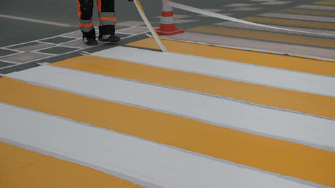 Road markings. Removing the masking tape after the paint application Live Action
