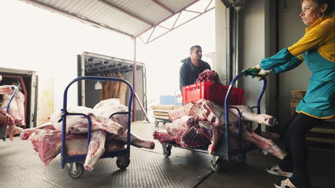 saleswoman and mover carry cart with meat in supermarket Live Action