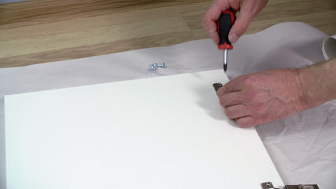 Male hand fixing screw with screwdriver on furniture loop while assembly Live Action