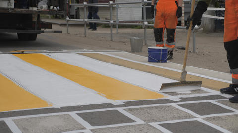 Road markings. Application of paint on asphalt from a bucket, distribution of road paint on the Live Action