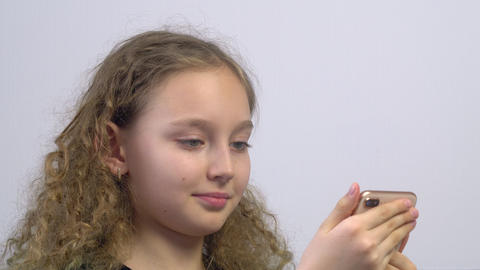 Portrait smiling girl teenager browsing social networks in mobile phone. Face Live Action