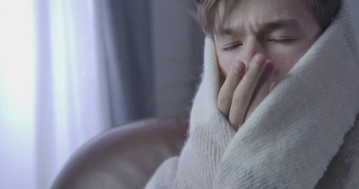 Extreme close-up of ill Caucasian boy coughing and rubbing eyes. Portrait of Live Action