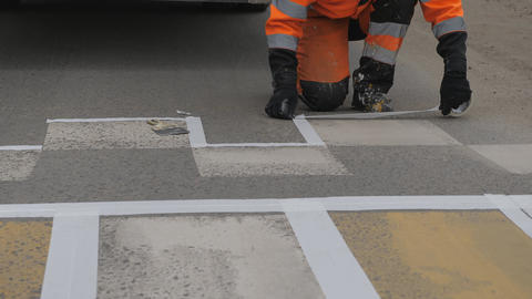 Road markings. Applying a paint stencil. Sticker of masking tape on the asphalt Live Action