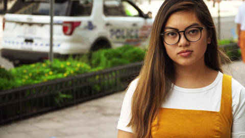 4K Young Minority Asian Woman with Neutral Expression in front of Police Vehicle Live Action