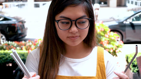 Asian Millennial Choosing Between Paper or Metal straws. Anti-Plastic concept Live Action