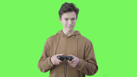 Portrait of happy millennial boy enjoying video game. Smiling Caucasian teenager Live Action