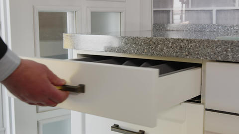 Opening a drawer for storing kitchen utensils. A man's hand opens a white drawer Live Action