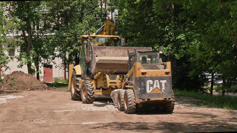 Two skid steer loaders moving sand soil at construction area outdoors Acción en vivo