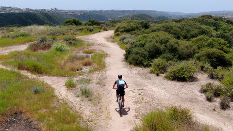 Aerial view of riding mountain bike in a small singletrack dry trail in the Acción en vivo