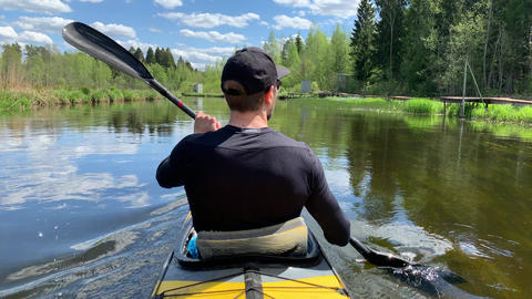 Russia, Gatchina, 29 May 2020: The young men in a cap floats on a kayak on the Acción en vivo