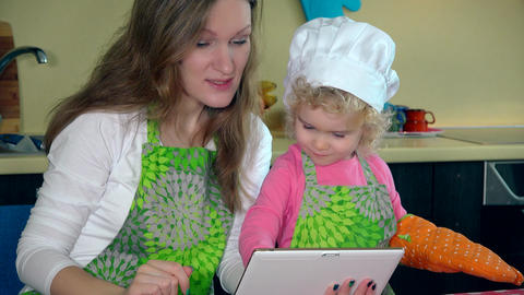 mother with daughter bakers looking for recipe on tablet in kitchen. 4K Acción en vivo
