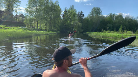 Russia, Gatchina, 29 May 2020: The two young men in a cap float on a kayak on Acción en vivo