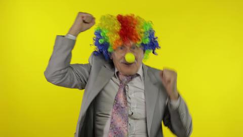 Elderly old clown businessman freelancer dancing, celebrate victory, entertains Live Action