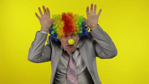 Elderly clown businessman entrepreneur boss making silly faces. Copy space Live Action
