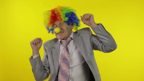 Elderly clown businessman entrepreneur boss dancing, entertains, celebrate Live Action