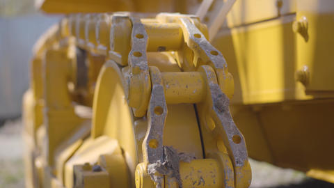Extreme close-up of yellow tracked tractor. Back view of part of industrial Live Action