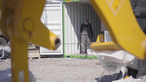 Professional construction workers unloading shipping container on production Live Action