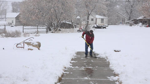 Winter snow storm man working to remove from sidewalk 4K 006 Footage