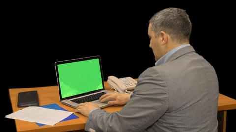 A man typing on a laptop computer with a green screen, alpha channel Footage