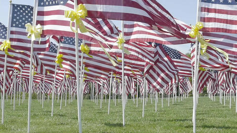Slow motion American flags with yellow ribbons waving in the wind Footage