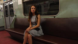 Young woman sit alone at empty subway car, dim illumination, old-style interior Footage