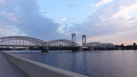 POV approach steel arched railway bridge across Neva River, nice evening clouds Footage