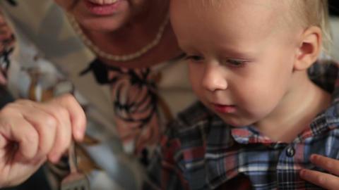 Grandmother feeding her little baby grandson Footage