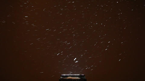 Snowflakes fly and swirl above light source, dark background, winter time Footage