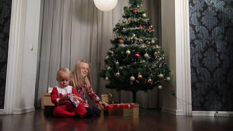 Little boy and girl opening presents on Christmas Footage