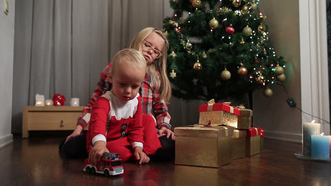 Happy children playing with toy car by Christmas tree Footage