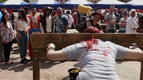 Wet sponge throwing game - woman in the stocks Footage