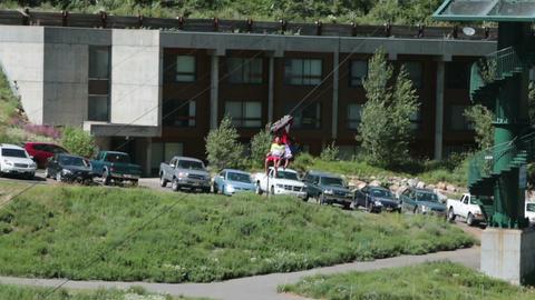 Zipline two boy friends ride down mountain resort HD 8602 Footage