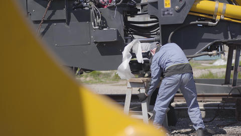 Workers in face masks fixing heavy industrial machinery outdoors. Employees Live Action