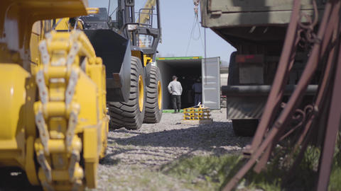 Caucasian construction workers checking equipment in shipping container at the Live Action