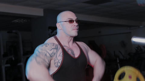 Professional bodybuilder performs an exercise lifting the barbell to the chin in GIF