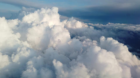Beautiful clouds illuminated by soft sunlight floating above land and forming Live Action