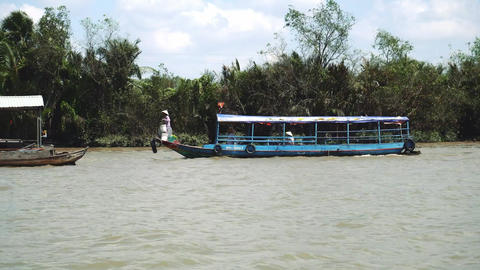 Traditional Vietnamese ferry boat taking people and their bicycles across the Live Action