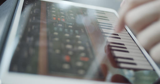 Playing digital midi piano instrument on a tablet touchscreen device Live Action