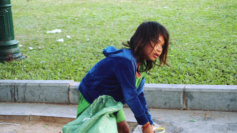 A Little girl Throws Garbage In The Trash In In The Capital Of Cambodia Phnom Live Action
