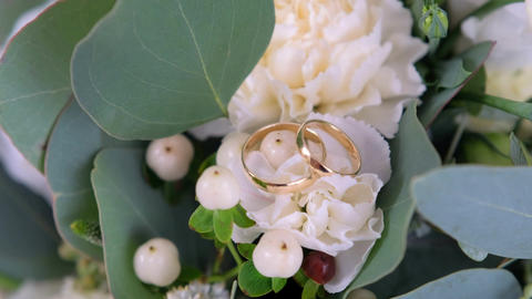 Wedding rings lying on the wedding bouquet Live Action