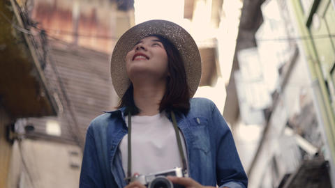 Smiling of female young Asian traveler wearing retro fedora hat walking and looking up around at a Live Action