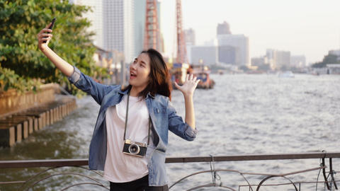 Beautiful Asian woman taking selfie video chat with her friends sharing enjoyment vacation summer Live Action