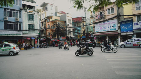 Motorbikes and other traffic navigate through busy streets, Vietnam, Hanoi Live Action