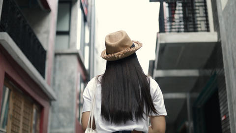 Attractive beautiful Asian girl walking and looking around a small street enjoying vacation summer Live Action