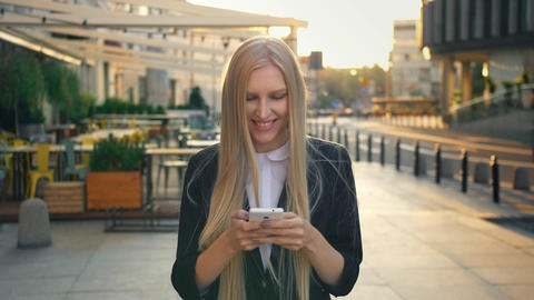 Formal business woman walking on street. Elegant blond girl in suit and walking Live Action
