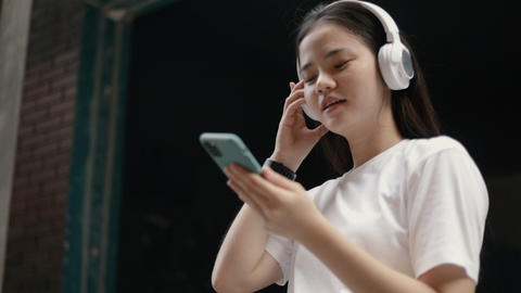 Attractive Asian woman wears headphones listening to music and using smartphone checking social Live Action