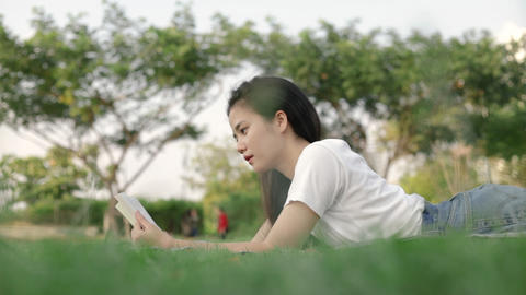 Beautiful asian woman relaxed reading a book while lying on the floor grass outdoors at a public Live Action