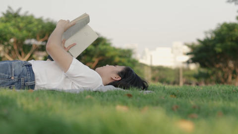 Attractive beautiful young Asian female relaxed reading a book while lying on the floor grass Live Action