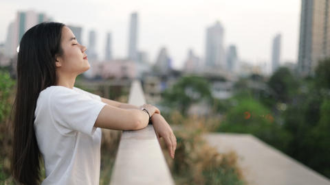 Portrait of beautiful Asian woman enjoying peaceful sunset and looking up exhaling fresh air Live Action