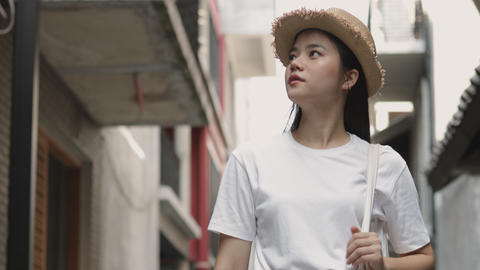 Attractive beautiful Asian female walking and looking around a small street enjoying vacation summer Live Action